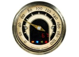 The image shows a front view of the Motogadget MST Vintage Gauge with lights on.